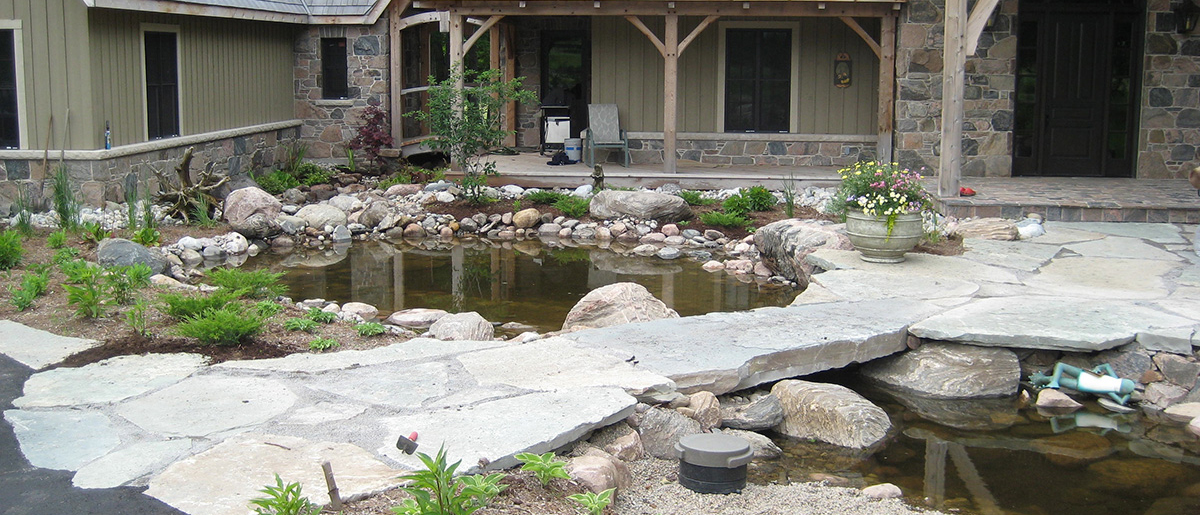Custom pond water feature in a backyard by Johnston's Greenhouse